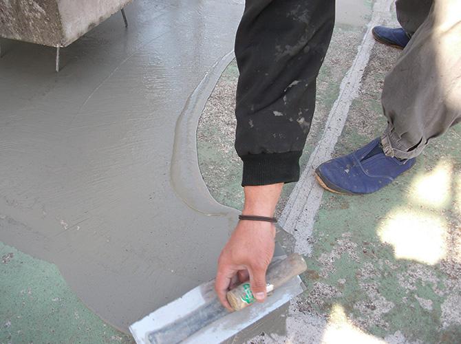 防水シートを張るための接着剤の塗布中です。