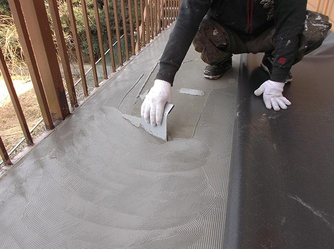 長尺シートの接着剤塗布施工中です。