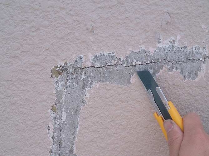 ひび割れ周辺の既存塗膜を剥離しているようすです。