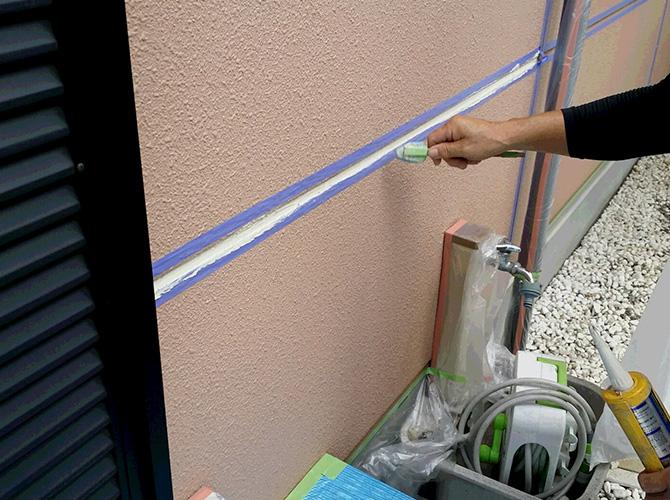 外壁のシーリング剤を均しているようすです。