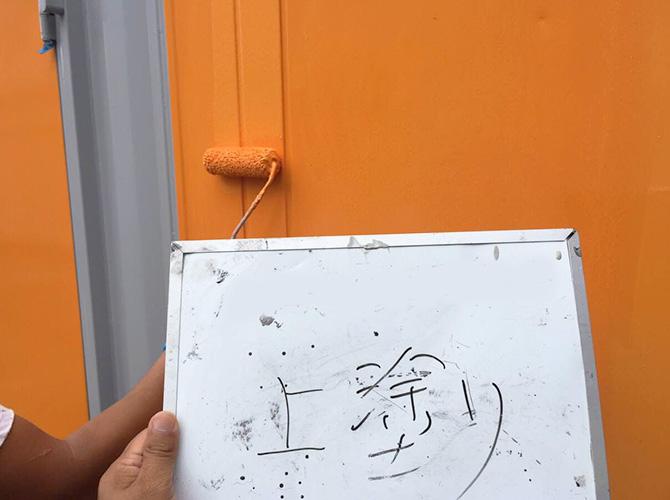 コンテナのオレンジ色での上塗り施工中です。