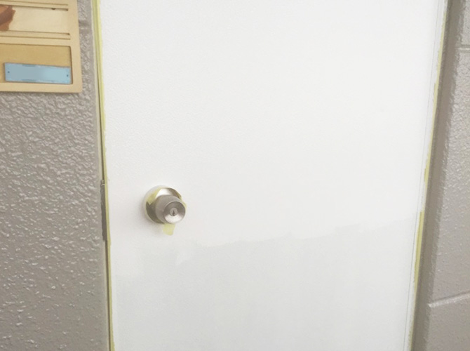 玄関ドア塗装の上塗り施工中のようすです。