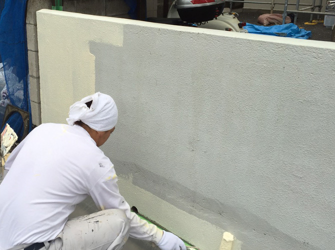 塀塗装の下塗り施工中のようすです。
