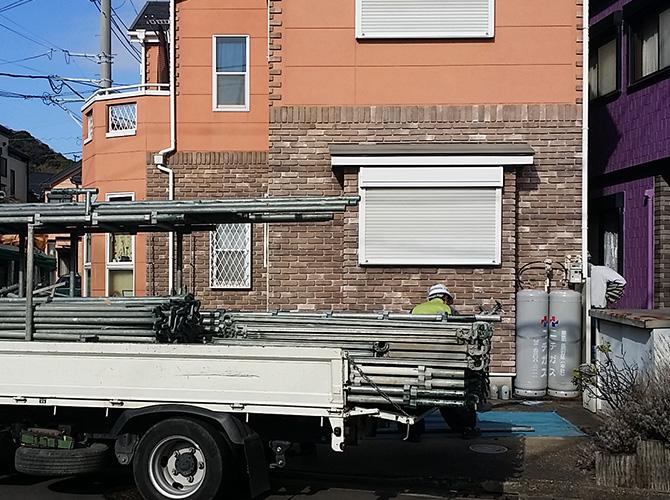 外観がオレンジが印象的な戸建住宅の架設足場の設置中
