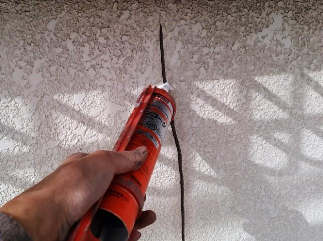 外壁のひび割れ個所にシーリング材を打ち込む